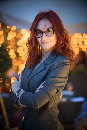 A business woman with red hair standing with her arms crossed Reklamní fotografie