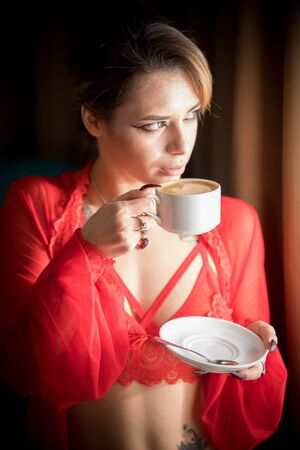 Young woman with tattoos in a sexy red underwear standing near the window and drinking a coffee Imagens