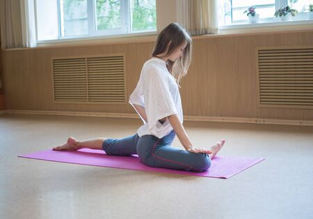 Young slim woman with blonde hair sitting on the yoga mat and doing stretching exercises