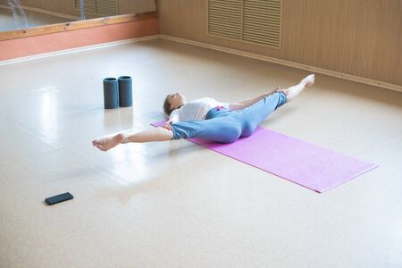 Young woman doing exercises on the yoga mat - performing a split and holding a balance - dance studio
