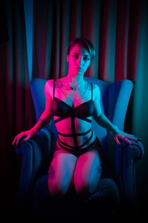 Young woman with tattoos in a sexy underwear sitting in a chair in neon lighting Imagens