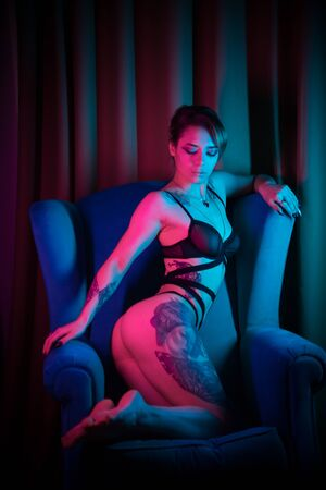 Young woman with many tattoos in a sexy underwear sitting in a chair in neon lighting Imagens
