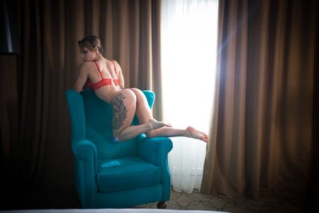 Young woman with tattoos in a sexy red underwear standing in the chair on her knees on the armrest Imagens