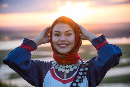 Young smiling woman in traditional russian clothes on a background of the sunset