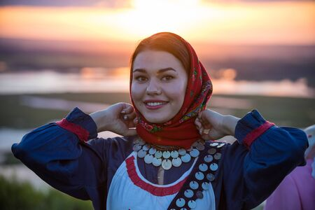 Young pretty smiling woman in traditional russian clothes on a background of the sunset