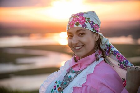 A smiling woman in traditional folk clothes on a background of the sunset Foto de archivo