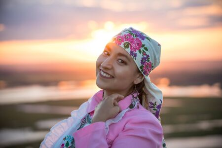 A smiling woman in traditional folk clothes on a background of the bright sunset
