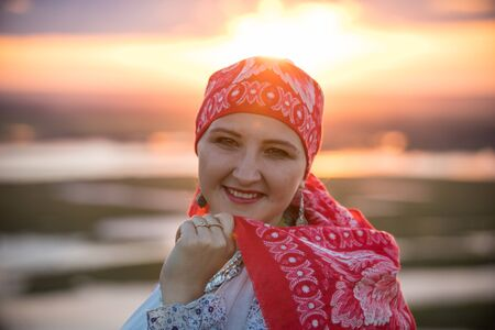 An adult smiling woman in traditional folk clothes on a background of the sunset Reklamní fotografie