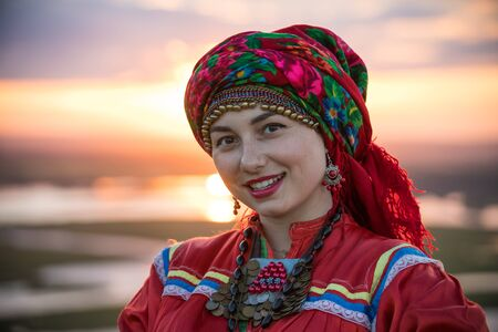Young smiling woman in traditional russian clothes and big red scarf on the head on a background of the sunset