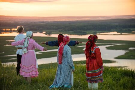 People in traditional russian clothes standing on the field and looking at the sunset