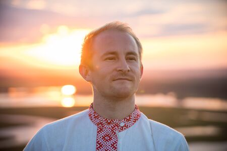 A man in traditional russian clothes standing on a background of the sunset