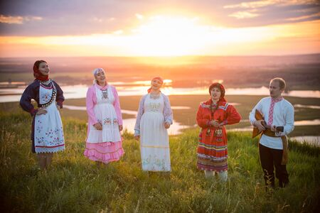 People in traditional russian clothes standing on the field on a background on the bright sunset - sing the song