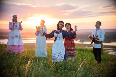 People in traditional russian clothes standing on the field on a background on the bright sunset - a woman dancing Reklamní fotografie