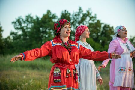Women in traditional russian clothes standing on the field and looking at the sunset