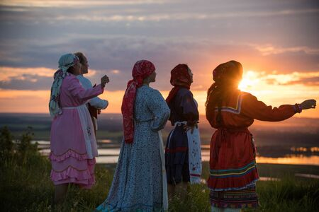 People in traditional russian clothes standing on the field and looking at the bright sunset