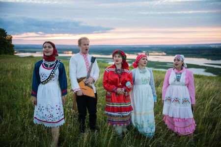People in traditional russian clothes standing on a green field and singing - a man holding balalaika Reklamní fotografie