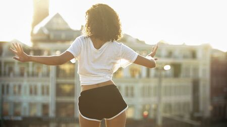 A young woman with curly hair in white shirt and small shorts dancing on the roof