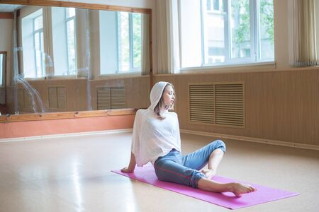 Young slim woman with blonde hair sitting on the yoga mat in dance studio and looking to the side