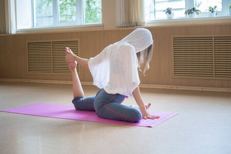 Young slim woman with blonde hair sitting on the yoga mat and doing stretching exercises - pulls the leg to the body Banque d'images