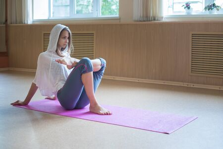 Young slim woman with blonde hair sitting on the yoga mat and stretching her leg - putting a foot on her knee