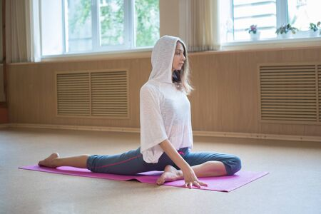 Young slim woman sitting on the yoga mat and doing stretching exercises in dance studio