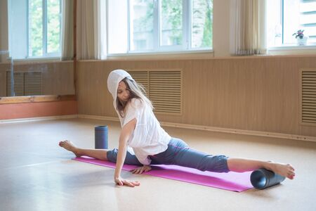 Young slim woman with blonde hair sitting on the yoga mat in split - using auxiliary stand under the foot - stretching one leg