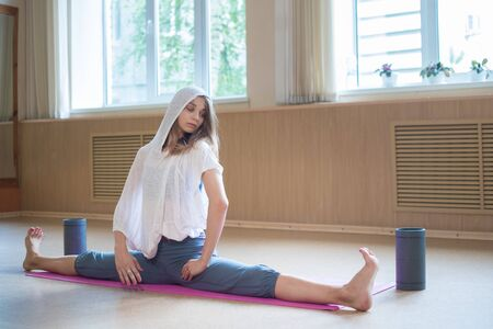 Young slim woman with blonde hair sitting on the yoga mat in horizontal split - dance studio Reklamní fotografie
