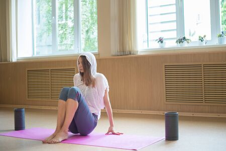 Young slim woman sitting on the yoga mat in dance studio Reklamní fotografie