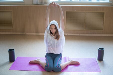 Young slim woman sitting on the yoga mat and pulling her hands up