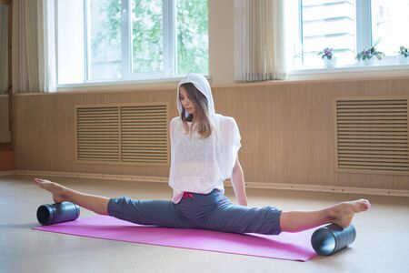 Young slim woman with blonde hair sitting on the yoga mat in split and training her stretching - using auxiliary stand under the feet