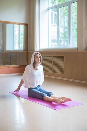 Young slim woman sitting on the yoga mat and pulling her toes forward