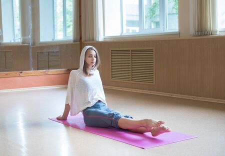 Young woman sitting on the yoga mat and pulling her toes forward