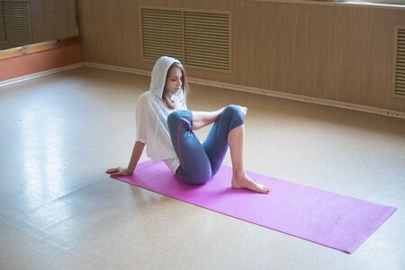 Young slim woman with blonde hair sitting on the yoga mat and stretching her leg