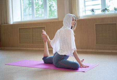 Young slim woman sitting on the yoga mat and doing stretching exercises - pulls the leg to the body Reklamní fotografie