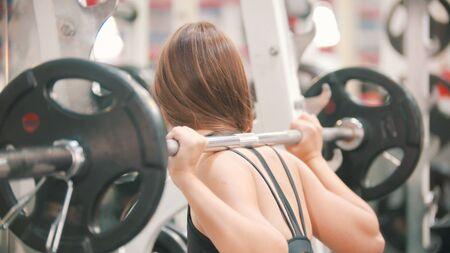 Una donna atleta che si allena in palestra - accovacciata con il manubrio sulle spalle Archivio Fotografico