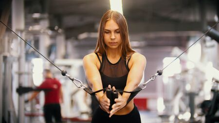 A sportive woman training in the gym - pulling the handles against herself - training hands