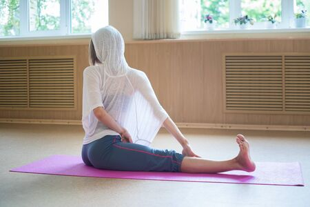 Young slim flexible woman sitting on the mat and going yoga