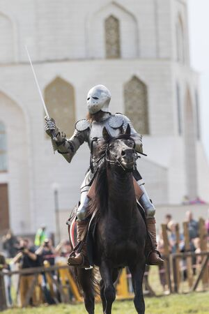 A man knight riding a horse on the battlefield - people watching behind the fence 스톡 콘텐츠