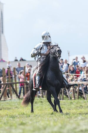 A man knight with a sword riding a horse on the battlefield - people watching behind the fence 스톡 콘텐츠 - 132084112