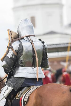 A man knight in helmet riding a brown horse