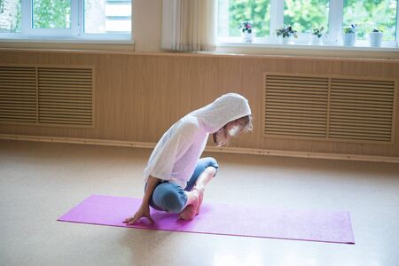 Young slim woman in white hood sitting on the yoga mat in lotus position leaning on her toes