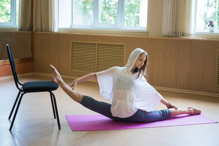 Young slim woman in white hoodie sitting on the yoga mat performing a split - doing leg stretching exercises using a chair Фото со стока