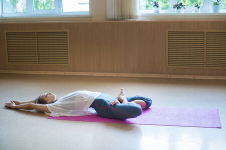 Young acrobatic woman with blonde hair sitting on the yoga mat in lotus pose and leaning back