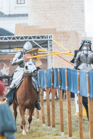 BULGAR, RUSSIA 11-08-2019: Knight Tournament at the medieval festival outdoors - a participant riding a brown horse in full armor and aiming in the opponent with a wooden spear