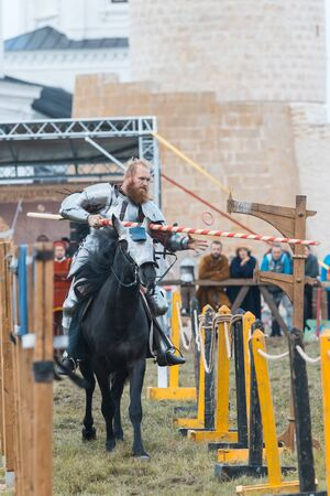 BULGAR, RUSSIA 11-08-2019: Knight riding through the path and takes the ring from the fence using a spear