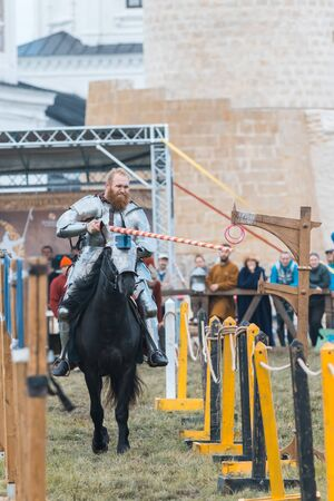 BULGAR, RUSSIA 11-08-2019: Knight riding a horse through the path and takes the ring from the fence with a spear - medieval festival