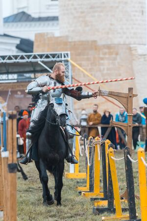 BULGAR, RUSSIA 11-08-2019: Knight riding a horse through the path and takes the ring from the fence using a spear - medieval festival