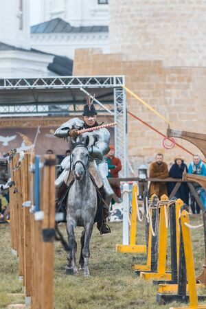 BULGAR, RUSSIA 11-08-2019: Knight riding through the path and takes the ring from the fence using a spear - medieval festival 新聞圖片