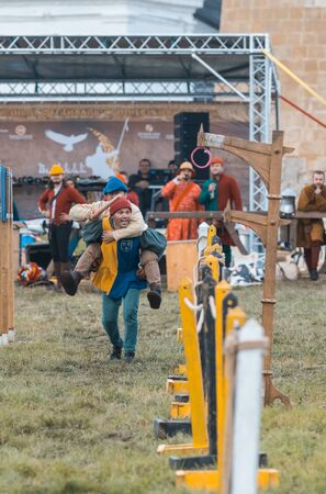 BULGAR, RUSSIA 11-08-2019: Two buffoons having fun on the battlefield on medieval festival - one man sitting on the back of another - holding a wooden spear
