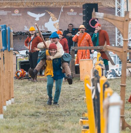 BULGAR, RUSSIA 11-08-2019: Two buffoons having fun on the battlefield on medieval festival - one man riding another - holding a wooden spear 新聞圖片